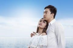 Azjatycka romantyczna para z dziewczyną opartą na jej chłopaku na plaży z powrotem zdjęcie stock