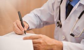 Azjatycka samiec lekarka pisze coś na schowku Obraz Stock