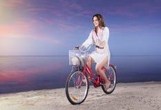 Azjatycka seksowna dziewczyna jedzie bicykl na pla?y przy zmierzchem obraz stock