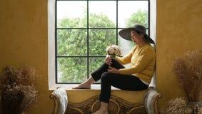 Azjatycka starsza kobieta siedzi w Europa stylu nadokiennym świetle słonecznym, luksusowa podróż zdjęcia royalty free