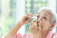 Azjatycka starsza kobiety k?adzenia oka kropla, zbli?enia starsza osoba u?ywa butelk? eyedrops w jej oczach widok, chory starej k zdjęcia stock