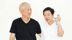 Azjatycka starsza para promuje pić dosyć wodnego wantowego hydrat obrazy royalty free