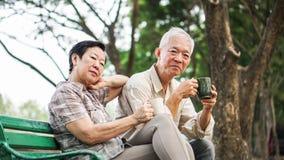 Azjatycka starsza para relaksuje pić kawę w lato parku, zieleń Obrazy Stock