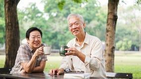 Azjatycka starsza para relaksuje pić kawę w lato parku, zieleń Fotografia Stock