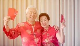 Azjatycka starsza para ?wi?tuje Chi?skiego nowego roku w czerwonym tradycyjnym kostiumu obraz stock