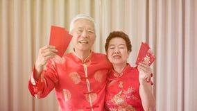 Azjatycka starsza para ?wi?tuje Chi?skiego nowego roku w czerwonym tradycyjnym kostiumu zdjęcie stock