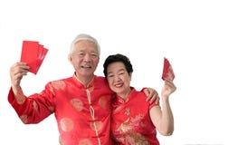 Azjatycka starsza para ?wi?tuje Chi?skiego nowego roku w czerwonym tradycyjnym kostiumu zdjęcie royalty free