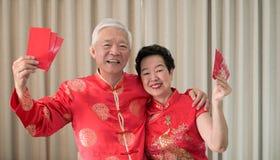 Azjatycka starsza para ?wi?tuje Chi?skiego nowego roku w czerwonym tradycyjnym kostiumu zdjęcia stock
