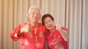 Azjatycka starsza para ?wi?tuje Chi?skiego nowego roku w czerwonym tradycyjnym kostiumu obrazy stock