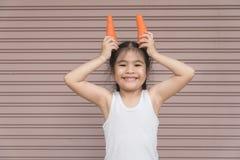Azjatycka szczęśliwa dziewczyna z marchewką Obrazy Royalty Free