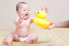 Azjatycka tajlandzka dziewczynka bawić się z żółtą kaczką Fotografia Royalty Free