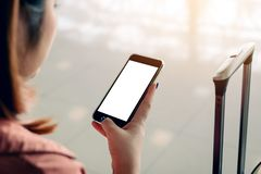 Azjatycka turystyczna kobieta czekać na lot w lotniskowym holu wręcza mienia i używać smartphone z pustym ekranem obraz stock
