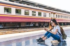 Azjatycka turystyczna nastoletnia dziewczyna przy dworcem używać smartphone mapę, ogólnospołeczną medialną odprawę lub zakup bile Zdjęcia Stock