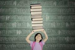 Azjatycka uczennica podnosi stos książki w bibliotece obraz stock