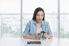 Azjatycki żeński shopaholic rozcięcie jej kredytowa karta z nożycami Zdjęcia Stock