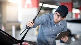 Azjatycki auto mechanik sprawdza przedniej szyby wiper obrazy royalty free