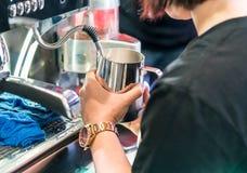 Azjatycki barista dekatyzuje świeżego mleko w nierdzewnym miotaczu z wentylacją zdjęcie royalty free