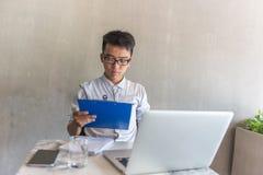 Azjatycki biurowy mężczyzna czyta pieniężnych dane na raporcie obraz stock