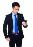 Azjatycki biznesmen czyta wiadomość na mądrze telefonie Obraz Royalty Free