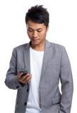 Azjatycki biznesmen czytający na telefonie komórkowym Obrazy Royalty Free