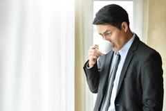 Azjatycki biznesmen pije gorącą kawę zdjęcia stock