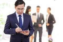 Azjatycki biznesmen pracuje z drużyną fotografia royalty free