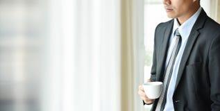 Azjatycki biznesmen trzyma filiżankę kawy obraz royalty free