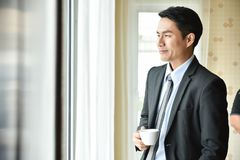 Azjatycki biznesmen trzyma filiżankę kawy fotografia stock