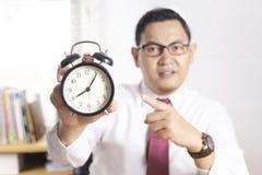 Azjatycki biznesmen Wskazuje przy zegarem, Gniewny wyrażenie obrazy royalty free