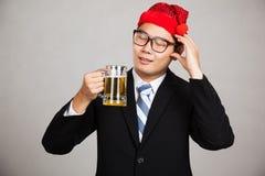 Azjatycki biznesmen z partyjnym kapeluszem dostaje opiłym z piwem Zdjęcia Stock