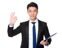 Azjatycki biznesmena mienie z schowkiem i ok znak gestykulujemy Fotografia Stock