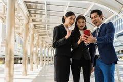 Azjatycki biznesowy mężczyzna i biznesowa kobieta robi konferenci telefonicznej telefonem komórkowym Obrazy Stock