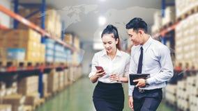 Azjatycki Biznesowy mężczyzna i Biznesowej kobiety pracownik w magazynowy używać Zdjęcia Stock