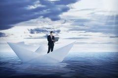 Azjatycki biznesowy mężczyzna pracuje z laptopem na papierowej łodzi zdjęcie royalty free