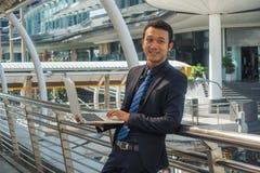 Azjatycki biznesowy mężczyzna trzyma laptop, sprawdza informację zdjęcia royalty free