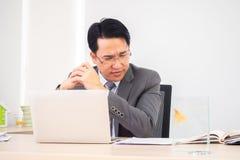 Azjatycki biznesowy mężczyzna w pracującym pokoju Poważna i myśląca akcja obrazy stock