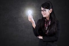 Azjatycki bizneswoman patrzeje jaskrawą żarówkę Zdjęcia Stock