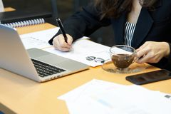 Azjatycki bizneswomanu writing sprzedaży raport z czarnym piórem Na biurku z notebookiem I sprzedaż raportu papier używać jako ba Obrazy Stock