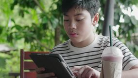 Azjatycki chłopak bawiący się na komputerze z uśmiechem zbiory