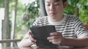 Azjatycki chłopak bawiący się na komputerze z uśmiechem zbiory wideo