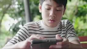 Azjatycki chÅ'opak bawiÄ…cy siÄ™ na komputerze z uÅ›miechem zdjęcie wideo