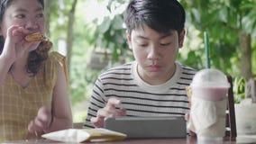 Azjatycki chłopak z siostrą lubi bawić się i jeść na tablecie zbiory wideo