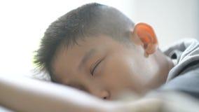 Azjatycki chłopiec dosypianie na łóżkowym pobliskim okno w domu zbiory