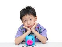 Azjatycki chłopiec główkowanie co kupować z jego savings zdjęcia stock