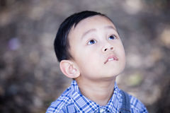 Azjatycki chłopiec lookingup outdoors Obrazy Stock