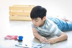 Azjatycki chłopiec lying on the beach i bawić się klingerytu blok w domu Zdjęcia Royalty Free