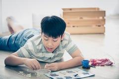 Azjatycki chłopiec lying on the beach i bawić się klingerytu blok w domu Obrazy Stock