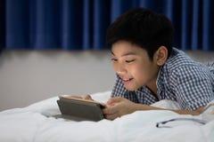 Azjatycki chłopiec lying on the beach i Bawić się W Domu gra Na Cyfrowej pastylce Zdjęcie Stock