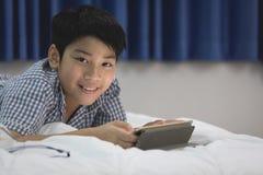 Azjatycki chłopiec lying on the beach i Bawić się W Domu gra Na Cyfrowej pastylce Zdjęcie Royalty Free