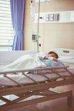 Azjatycki chłopiec lying on the beach na sickbed z zasolony śródżylnym (IV) zdrowy Fotografia Stock
